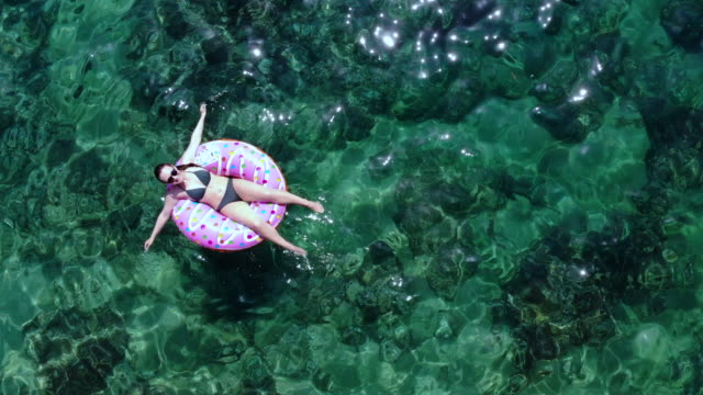 vídeos de stock e filmes b-roll de aerial view of happy woman in inflatable donuts with transparent water in the sea. - fotografar