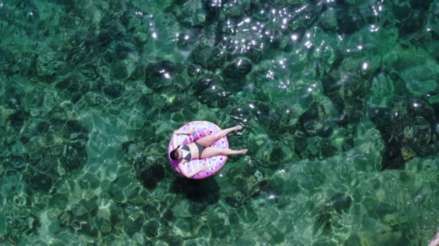 aerial view of happy woman in inflatable donuts with transparent water in the sea. - rubber ring stock videos & royalty-free footage