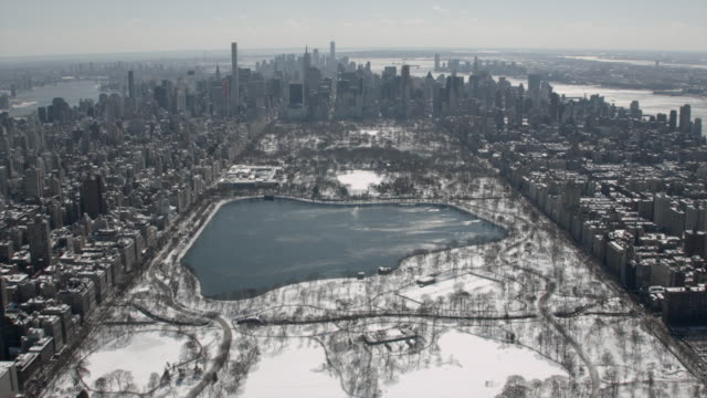 stockvideo's en b-roll-footage met aerial view of harlem streets panning up to central park with snow in new york city - central park manhattan
