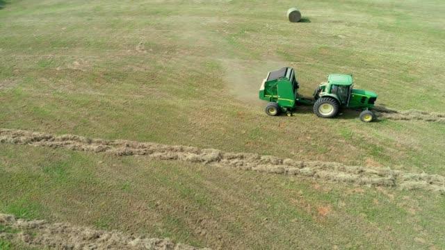aerial view of heavy john deere machinery baling hay in mapleton texas - hay baler stock videos & royalty-free footage