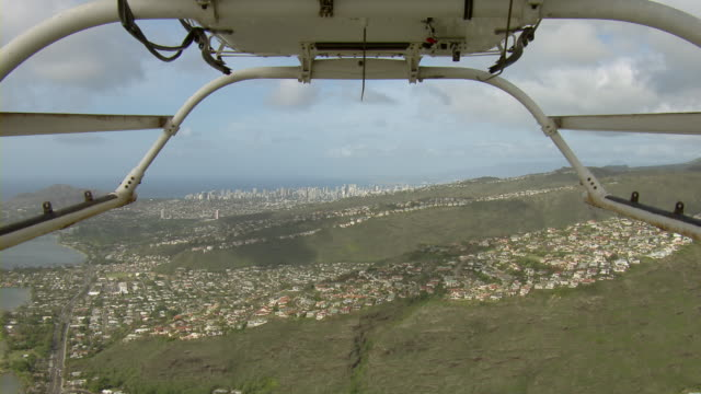 aerial view of helicopter flying over coastal suburbs in honolulu, hawaii with skyscrapers in the distance. - hawaii islands stock videos & royalty-free footage