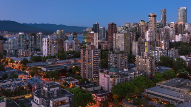 T/L Aerial view of high Rises in West End and Coal Harbour neighbourhoods of Vancouver at twilight / Vancouver, British Columbia, Canada