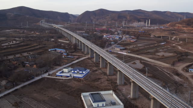 aerial view of high speed railway across a village in china - high speed train stock videos & royalty-free footage