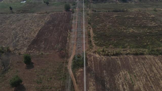 vista aerea 4k dei piloni elettrici della linea elettrica ad alta tensione sul campo - traliccio elettrico video stock e b–roll