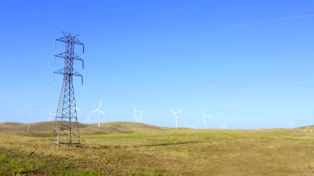 aerial view of high voltage power lines, transmission towers and wind turbines in fields on a sunny day in northern california. electric power industry and nature environment concepts. - power cable stock videos & royalty-free footage