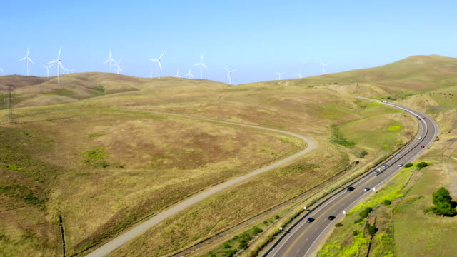 aerial view of high voltage power lines, transmission towers and wind turbines in fields on a sunny day in northern california. electric power industry and nature environment concepts. - electricity pylon stock videos & royalty-free footage