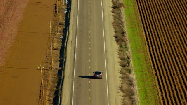vidéos et rushes de aerial view of highway beside farming fields california - ligne à haute tension
