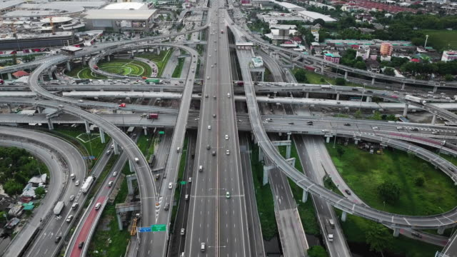 aerial view of highway junction with traffic in bangkok city, thailand - air pollution stock videos & royalty-free footage