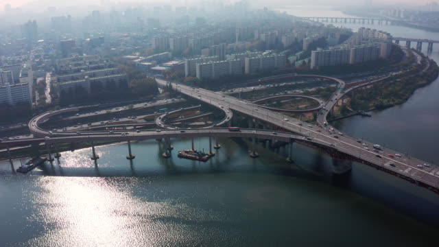aerial view of highway road junctions. the intersecting freeway road overpass of seoul downtown city skyline with vehicle on expressway and bridge cross over han river in seoul city, south korea. - korea stock videos & royalty-free footage