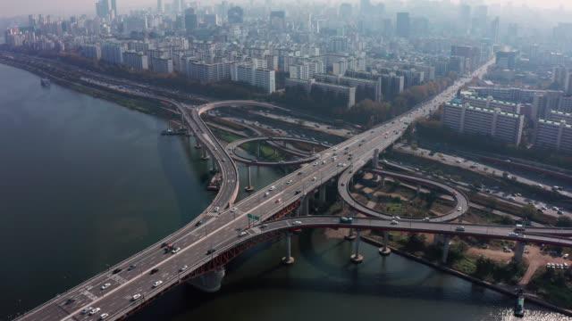 高速道路の道路ジャンクションの航空写真。ソウル市のダウンタウンのスカイラインの交差する高速道路の道路陸橋は、高速道路や橋の上の車両と韓国のソウル市の漢川を渡ります。 - ソウル点の映像素材/bロール