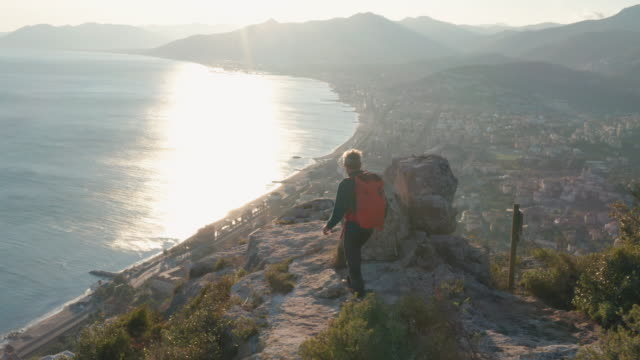 aerial view of hiker approaching hilltop at sunrise - at the edge of stock videos & royalty-free footage