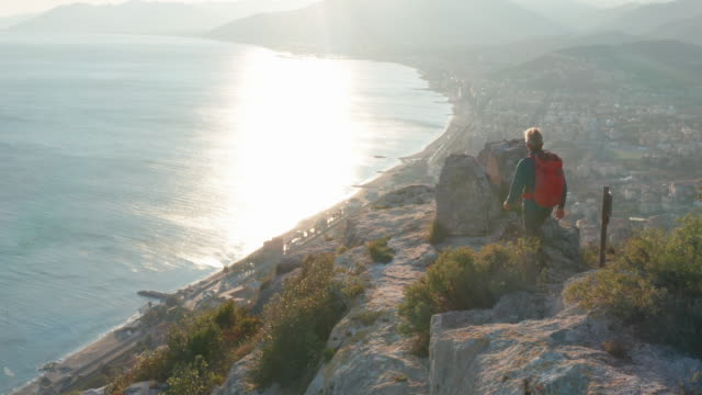 aerial view of hiker approaching hilltop at sunrise - sunrise dawn stock videos & royalty-free footage