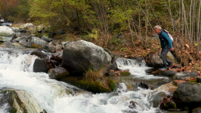 vidéos et rushes de aerial view of hiker exploring creek - chute d'eau