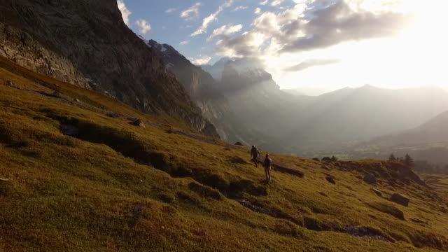 Aerial (drone) view of hikers ascending alpine meadow at sunset