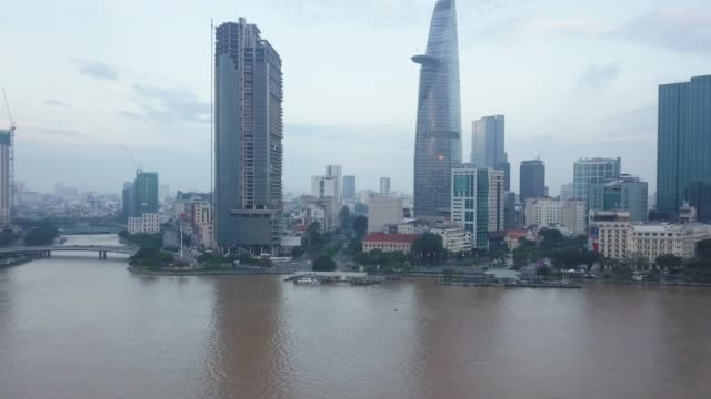 aerial view of ho chi minh city skyline and skyscrapers in center of heart business at ho chi minh city downtown. panorama of cityscape on saigon river in ho chi minh city at vietnam at sunrise scene - vietnam stock videos & royalty-free footage