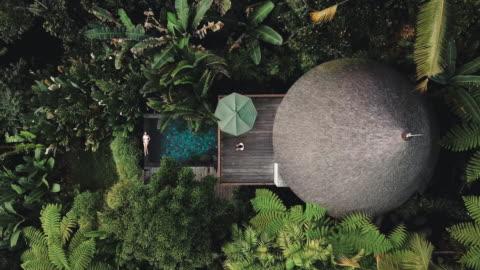 stockvideo's en b-roll-footage met luchtfoto van het vakantie weekend ontspannen in luxe met tropisch jungle villa bali, indonesië - bali