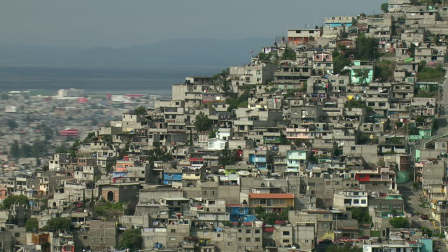 Aerial view of homes on crowded hillside in Mexico City.