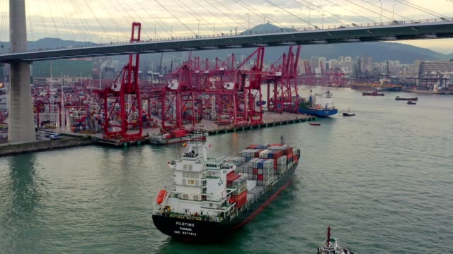 aerial view of hong kong kwai tsing container terminals and stonecutters bridge at dusk - global communications stock videos & royalty-free footage