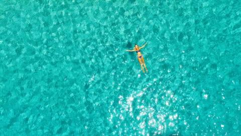 vídeos y material grabado en eventos de stock de aerial view of hot girl floating in the water in amazing, unspoiled and idyllic beach - plano descripción física