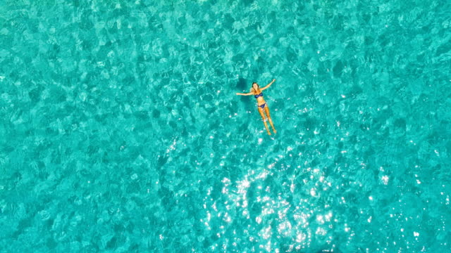 aerial view of hot girl floating in the water in amazing, unspoiled and idyllic beach - galleggiare sull'acqua video stock e b–roll