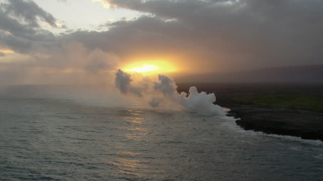 aerial view of hot lava flowing into ocean at hawaii volcanoes national park at sunset. - big island hawaii islands stock videos & royalty-free footage