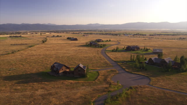 aerial view of houses in remote landscape near mountains / driggs, idaho, united states - idaho stock videos & royalty-free footage