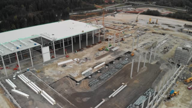 aerial view of huge construction site in progress by the highway - crane construction machinery stock videos & royalty-free footage