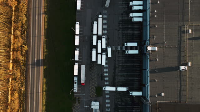 aerial view of huge warehouse with trucks near highway - 上部分点の映像素材/bロール