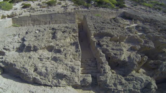 aerial view of human-made excavations in ibiza's rocky coastline, spain - rocky coastline stock videos & royalty-free footage