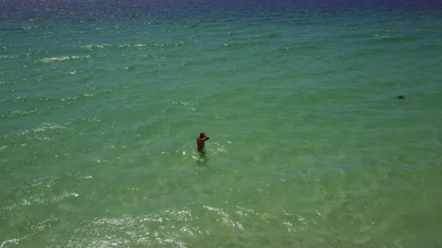 vídeos de stock e filmes b-roll de 4k aerial view of hyams beach with one man getting into the sea and swimming, jervis bay, australia - só um homem de idade mediana