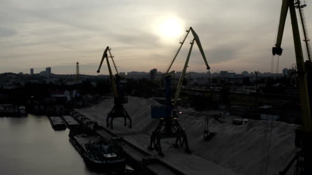 aerial view of industrial cranes loading sand in river port - キエフ市点の映像素材/bロール