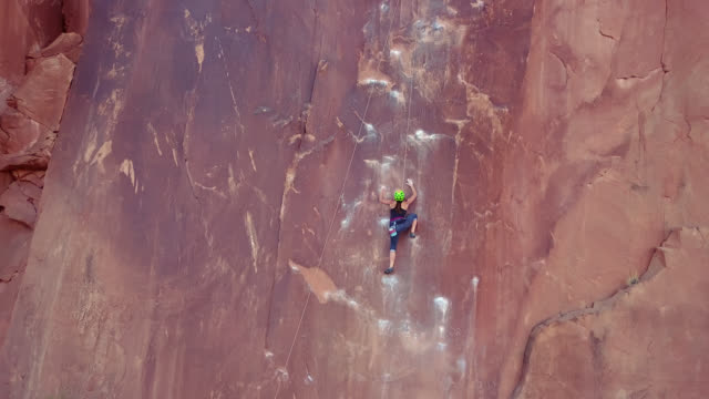 aerial view of intrepid rock climber ascending the sandstone rock face known as wall street in moab. - klättring bildbanksvideor och videomaterial från bakom kulisserna