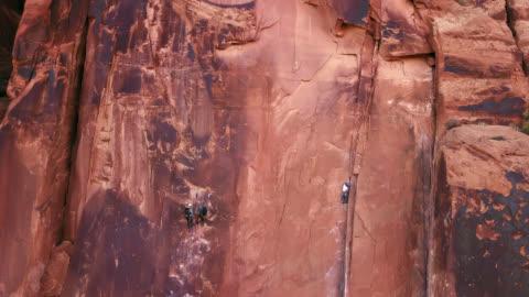 vídeos y material grabado en eventos de stock de aerial view of intrepid rock climbers ascending the sandstone rock face known as wall street in moab. - deporte de riesgo