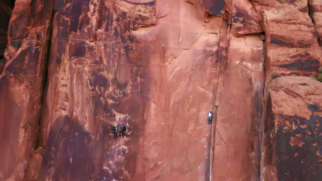 vídeos y material grabado en eventos de stock de aerial view of intrepid rock climbers ascending the sandstone rock face known as wall street in moab. - arenisca