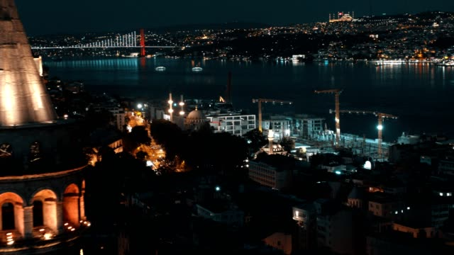 vídeos de stock e filmes b-roll de aerial view of istanbul bosphorus bridge behind the galata tower at night - istambul
