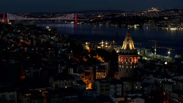 aerial view of istanbul bosphorus bridge behind the galata tower at night - cinematography stock videos & royalty-free footage