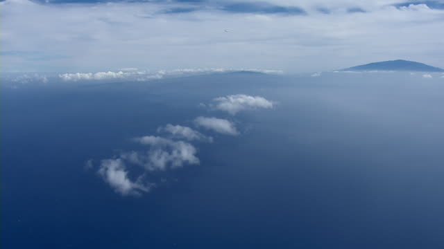 aerial view of jetliner flying over the blue pacific ocean with the island of hawaii in the distance. - big island hawaii islands stock videos & royalty-free footage