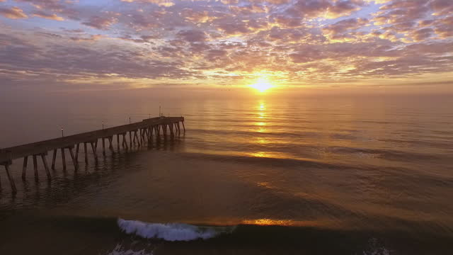 drone. aerial view of johnny mercer's pier as waves roll to shore and birds fly across the horizon during epic sunrise - stimmungsvoller himmel stock-videos und b-roll-filmmaterial
