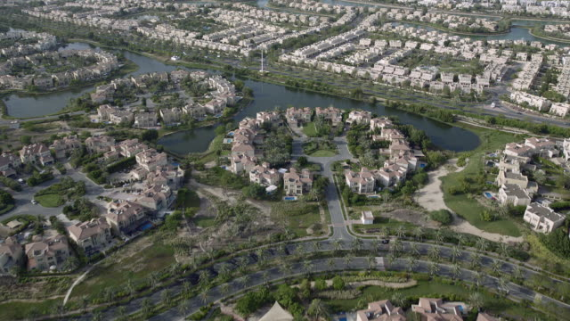 aerial view of jumeirah islands and emirates hills housing developments in dubai, united arab emirates. - villa stock videos & royalty-free footage