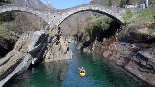 luftaufnahme des kanuten paddeln durch klare flusswasser unter steinbrücke - kajak stock-videos und b-roll-filmmaterial