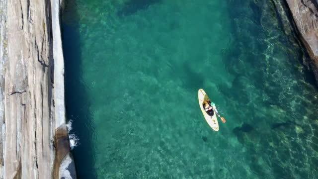 Luftaufnahme des Kanuten Paddeln durch klare Flusswasser