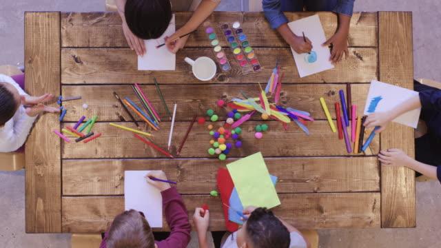 美術工芸をやっている子供たちの空中ビュー - 学校備品点の映像素材/bロール