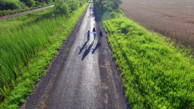 Aerial View of Kids Running Down Dirt Road