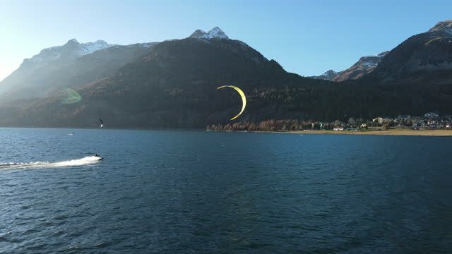 aerial view of kite surfer on alpine lake under snow capped mountains - exploration stock videos & royalty-free footage