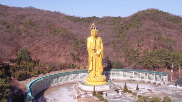 Aerial view of Kṣitigarbha (Golden Stone Buddha) in Mitasa Temple and mountain range