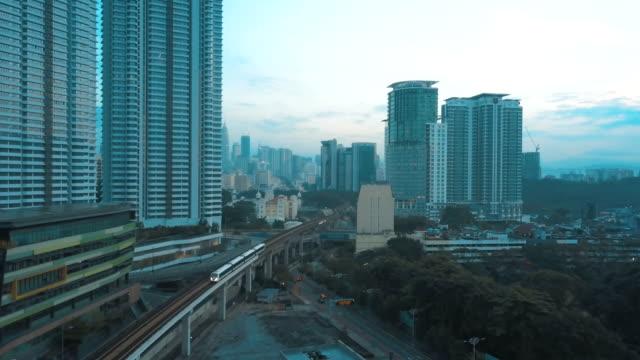 vidéos et rushes de vue aérienne de kl sentral et paysage urbain, skytrain à kuala lumpur à la lumière du soleil - tour menara kl