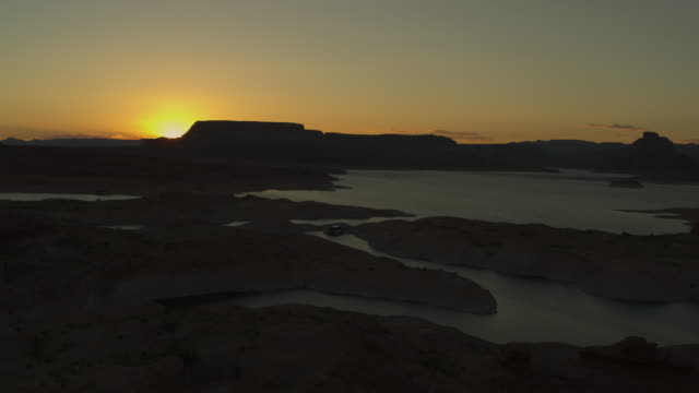 vídeos y material grabado en eventos de stock de aerial view of lake and silhouette of landscape at sunset / glen canyon, utah, united states - lago powell