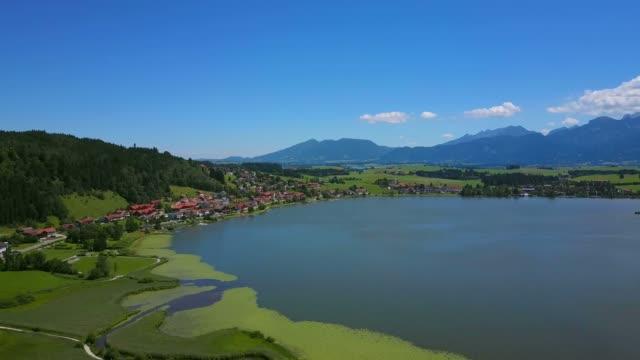 aerial view of lake hopfensee and hopfen am see near fussen, allgau, swabia, bavaria, germany, europe - ruhige szene stock-videos und b-roll-filmmaterial