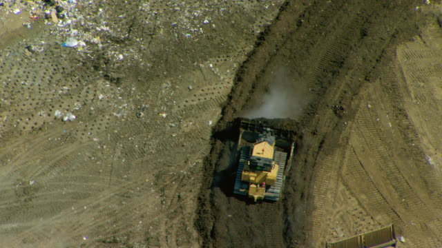 Aerial view of landfill where bulldozers are being used to move and cover waste with dirt.