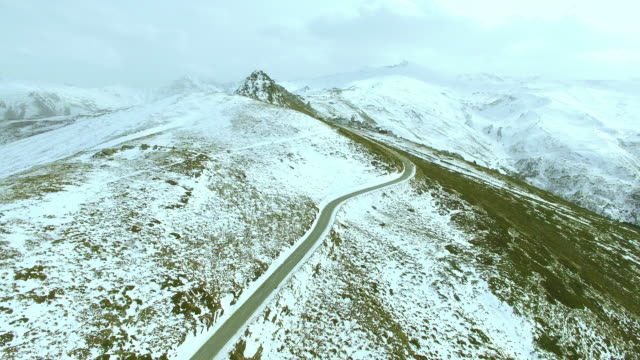 aerial view of landscape of mountains with snow and forest with a lonely road - silvestre bildbanksvideor och videomaterial från bakom kulisserna
